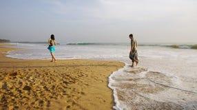 Garçon et fille marchant sur la plage. Photos stock