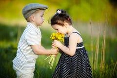 Garçon et fille mignons sur la zone d'été photographie stock libre de droits