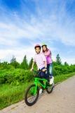 Garçon et fille montant le même vélo qui chacun des deux se tiennent Photographie stock libre de droits