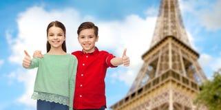 Garçon et fille montrant des pouces au-dessus de Tour Eiffel Image stock