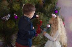 Garçon et fille occupés décorant un arbre de Noël Photos libres de droits
