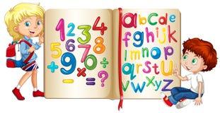 Garçon et fille par le livre des nombres et des alphabets Photo stock