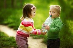 Garçon et fille partageant la bouteille de l'eau Photo libre de droits