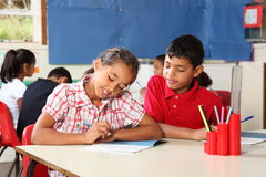 Garçon et fille pendant la leçon d'école dans la salle de classe Image libre de droits