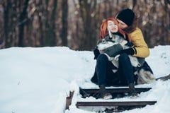 Garçon et fille posant dans les étapes couvertes de neige Images stock