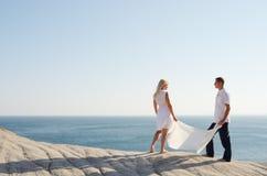 Garçon et fille retenant un châle blanc, près de la mer Photos stock
