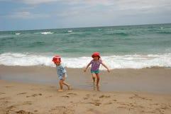 Garçon et fille runing de la vague déferlante d'océan photographie stock
