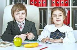 Garçon et fille s'asseyant à une table dans les écoliers Photos stock