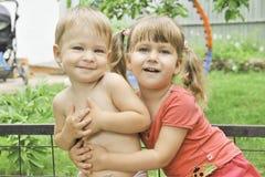 Garçon et fille s'asseyant côte à côte sur le banc, étreindre, souriant Photos libres de droits