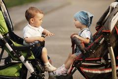 Garçon et fille dans des voitures d'enfant Photographie stock libre de droits