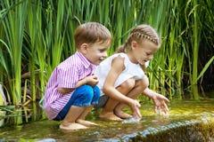 Garçon et fille s'asseyant dans l'eau près de la petite cascade Photographie stock