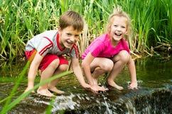 Garçon et fille s'asseyant dans l'eau près de la petite cascade Images stock