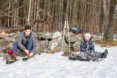 Garçon et fille s'asseyant dans la neige mettant sur leurs skis contre un mur en pierre Photo stock