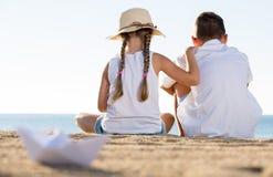 Garçon et fille s'asseyant de retour Photographie stock libre de droits