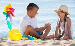 garçon et fille s'asseyant ensemble sur la plage sablonneuse Photos stock