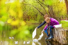 Garçon et fille s'asseyant près de l'étang mettant les bateaux de papier Photo libre de droits