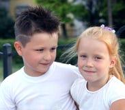 Garçon et fille s'asseyant s'embrassant Photographie stock libre de droits