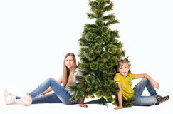 Garçon et fille s'asseyant sous l'arbre Image stock