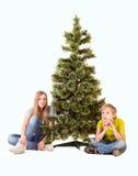 Garçon et fille s'asseyant sous l'arbre de Noël Images libres de droits
