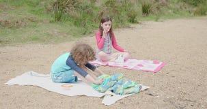 Garçon et fille s'asseyant sur des serviettes de plage, peu de fille mangeant un biscuit banque de vidéos