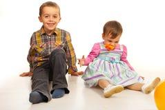 Garçon et fille s'asseyant sur l'étage Photographie stock
