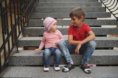 Garçon et fille s'asseyant sur l'escalier Photo libre de droits