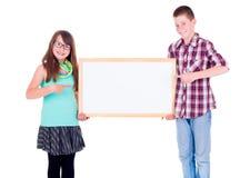 Garçon et fille se dirigeant sur le conseil vide Image stock