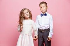 Garçon et fille se tenant dans le studio sur le fond rose Image libre de droits