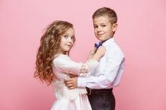 Garçon et fille se tenant dans le studio sur le fond rose Photos stock