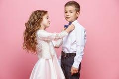Garçon et fille se tenant dans le studio sur le fond rose Photographie stock libre de droits