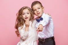 Garçon et fille se tenant dans le studio sur le fond rose Images libres de droits