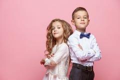 Garçon et fille se tenant dans le studio sur le fond rose Image stock