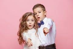 Garçon et fille se tenant dans le studio sur le fond rose Photo libre de droits