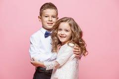 Garçon et fille se tenant dans le studio sur le fond rose Photos libres de droits