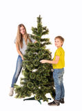 Garçon et fille se tenant près de l'arbre de Noël Photographie stock libre de droits