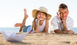 Garçon et fille se trouvant sur la plage sablonneuse Photographie stock