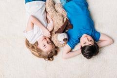Garçon et fille se trouvant sur le tapis avec l'ours de nounours à la maison et regardant l'appareil-photo Image stock