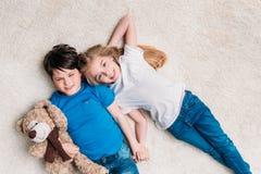 Garçon et fille se trouvant sur le tapis avec l'ours de nounours à la maison et regardant l'appareil-photo Photo libre de droits