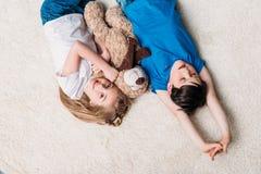 Garçon et fille se trouvant sur le tapis avec l'ours de nounours à la maison et regardant l'appareil-photo Photo stock