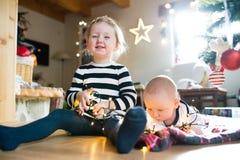 Garçon et fille sous l'arbre de Noël empêtré dans la chaîne des lumières Photos stock