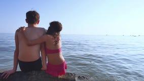 Garçon et fille sur la mer Un garçon et une fille s'asseyent sur les roches sur la vue de mer de derrière d'un romance heureux Photographie stock libre de droits