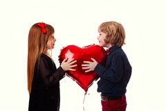 Garçon et fille sur un fond blanc tenant un coeur de rouge de ballon Images stock