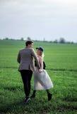 Garçon et fille tenant des mains et le fonctionnement dehors Photographie stock libre de droits