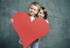 Garçon et fille tenant un coeur de jouet Photographie stock