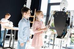 Garçon et fille vérifiant le mécanisme de la main de robot Images stock