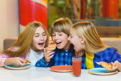 Garçon et filles de sourire mangeant de la pizza ou buvant du jus d'intérieur Image stock