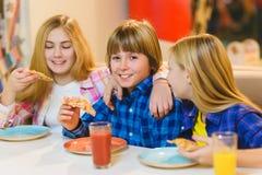 Garçon et filles de sourire mangeant de la pizza ou buvant du jus d'intérieur Images stock