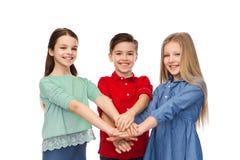 Garçon et filles heureux avec des mains sur le dessus Photo stock
