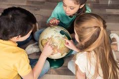 Garçon et filles recherchant des pays sur le globe Photos libres de droits
