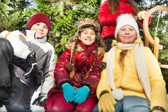 Garçon et filles s'asseyant ensemble dehors dans la neige Image stock